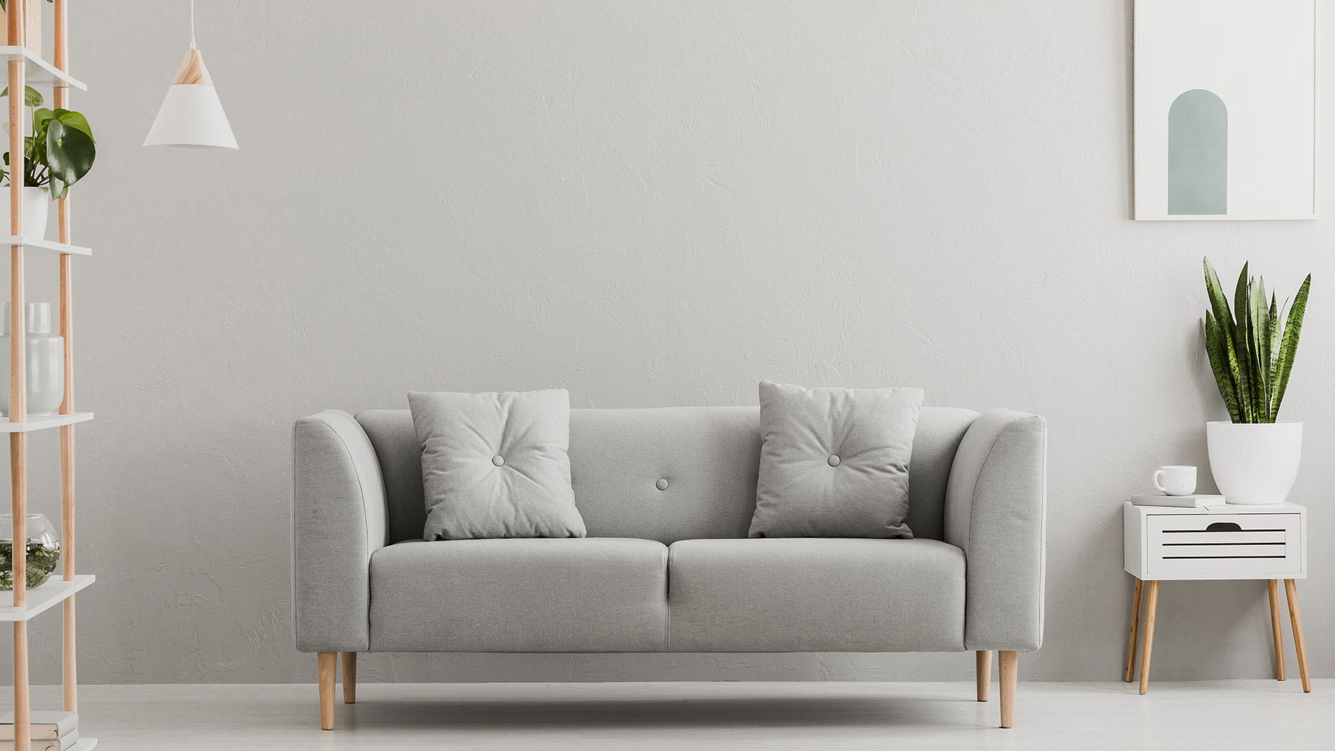 A grey couch looking clean after housekeeping
