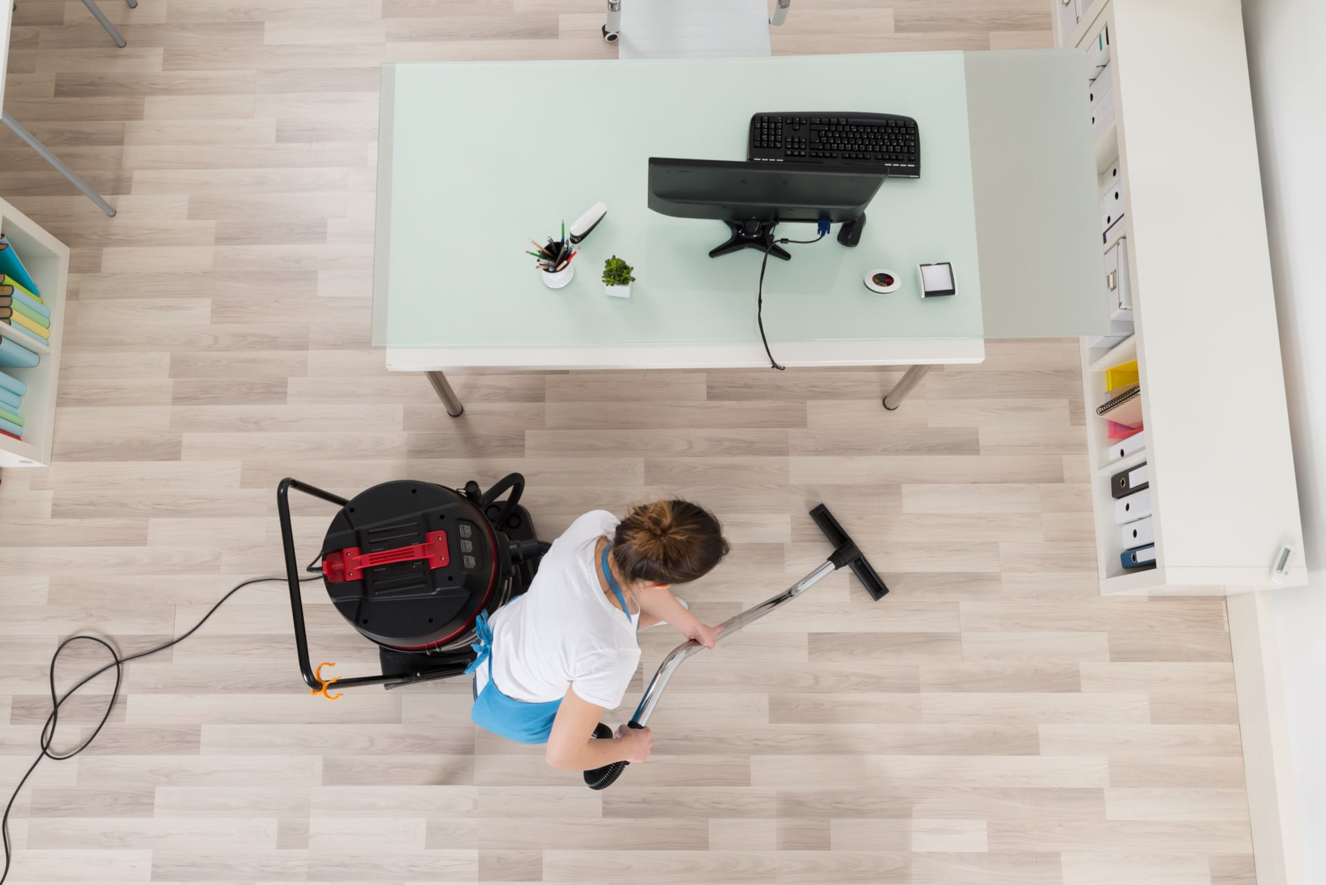 A woman vacuuming under an office during commercial cleaning services