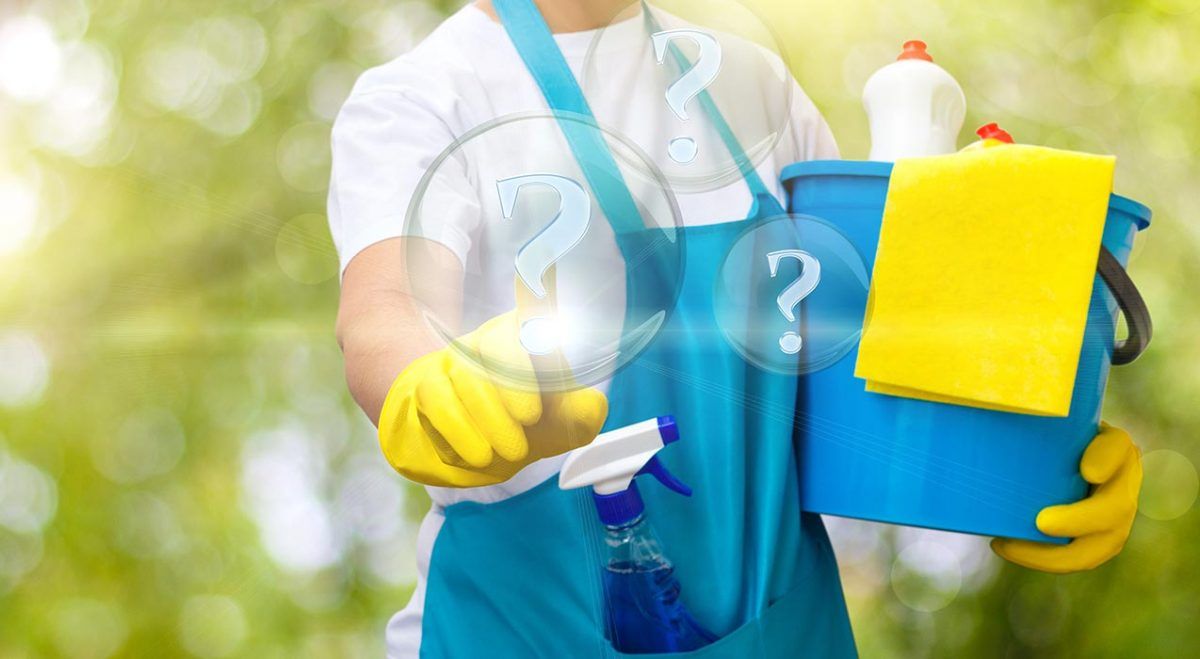 A maid with a cleaning company with a basket of cleaning supplies