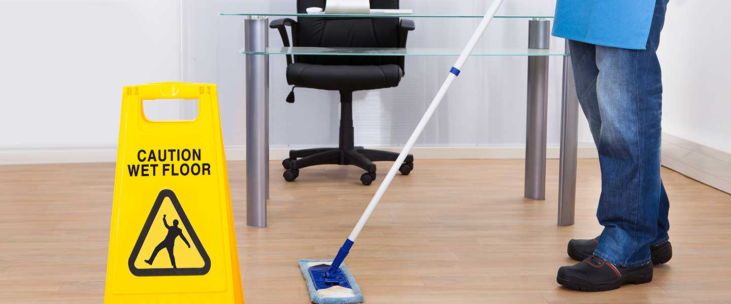 A woman mopping an office during commercial cleaning