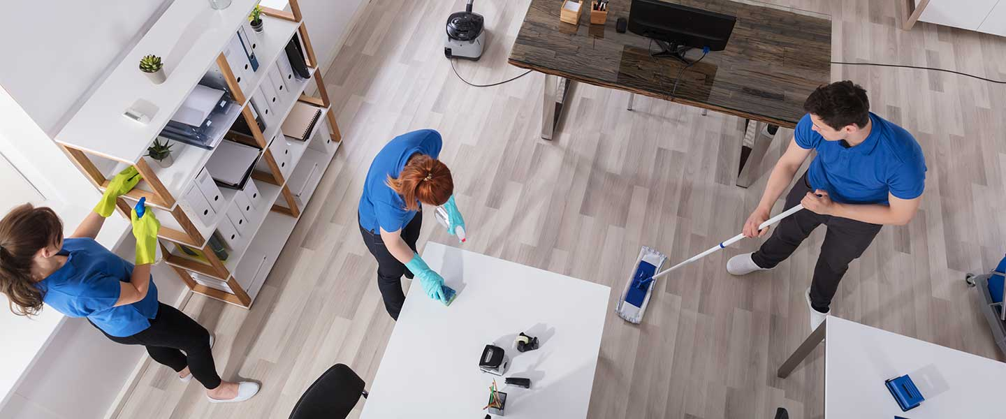 A team of cleaners work to tidy an office space