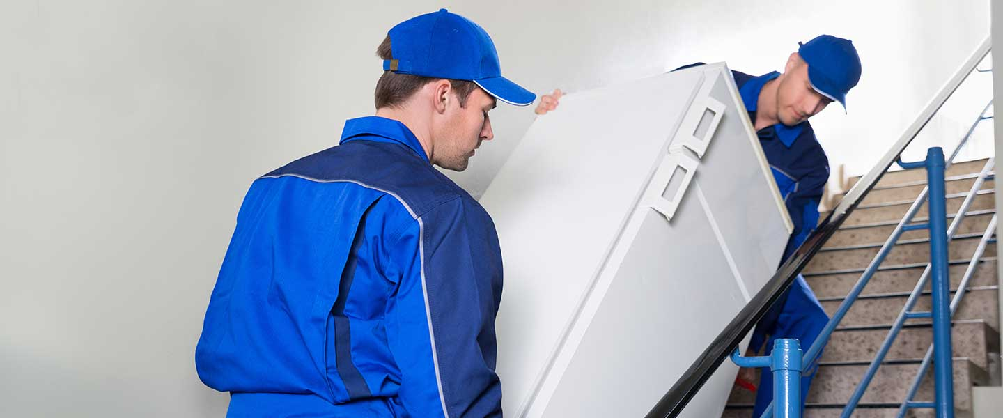 Professional movers move a refrigerator up stairs