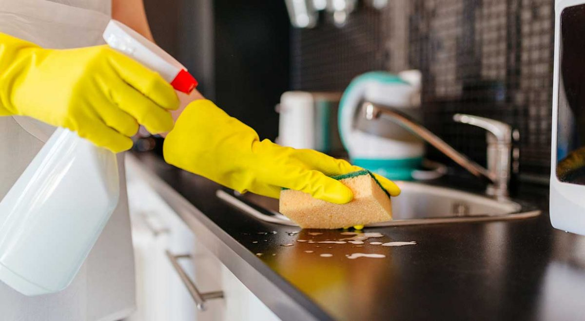 A woman wiping down a sink during house cleaning