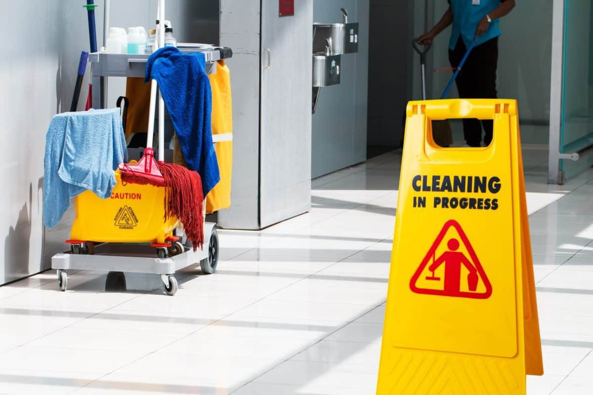 A cart with cleaning supplies being used for janitorial services.